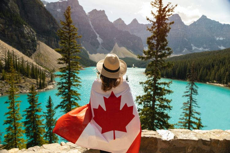 A woman looks out over a lake, mountains and trees, her back is to the camera, and she wears a hat. She is wrapped in a Canadian flag.