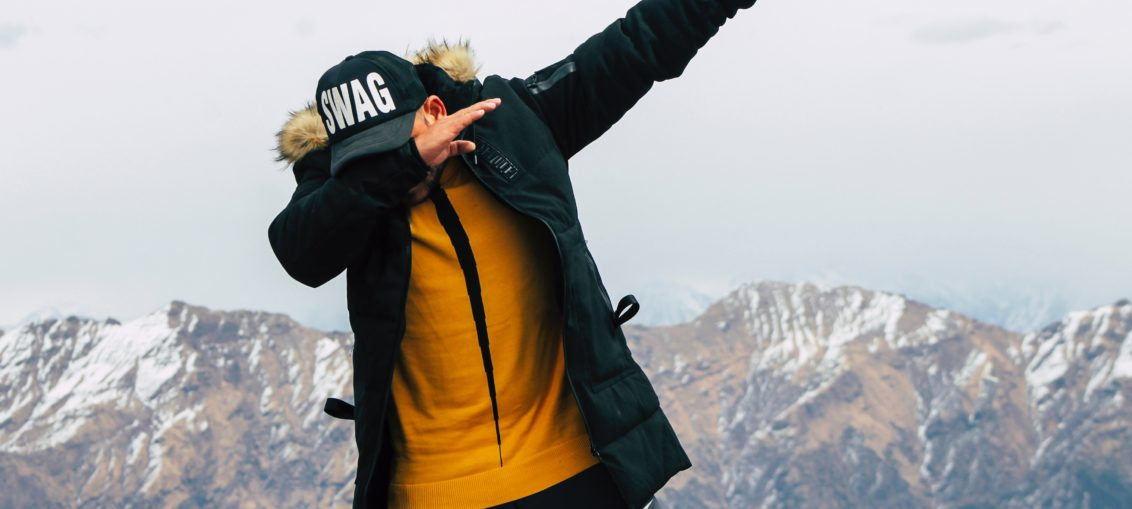 """A man in a parka and ball cap reading Swag does """"The Dab"""" move"""