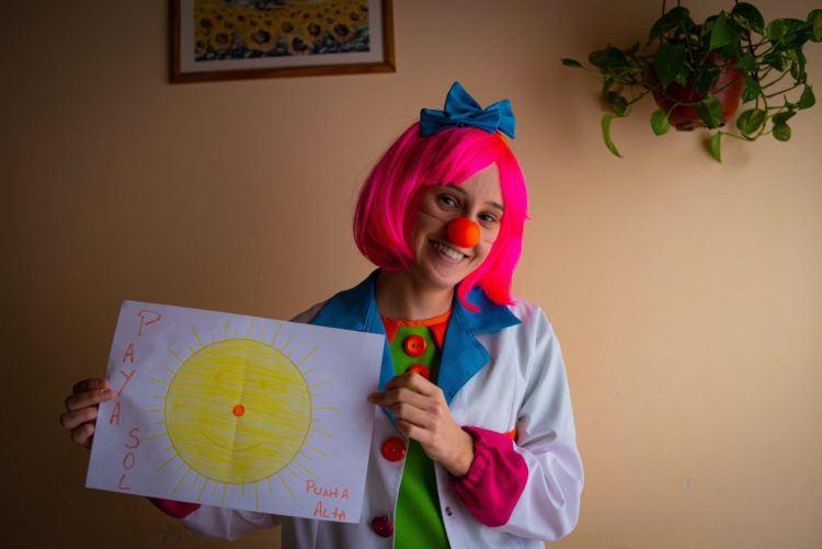 A woman dressed as a clown holds a large piece of paper