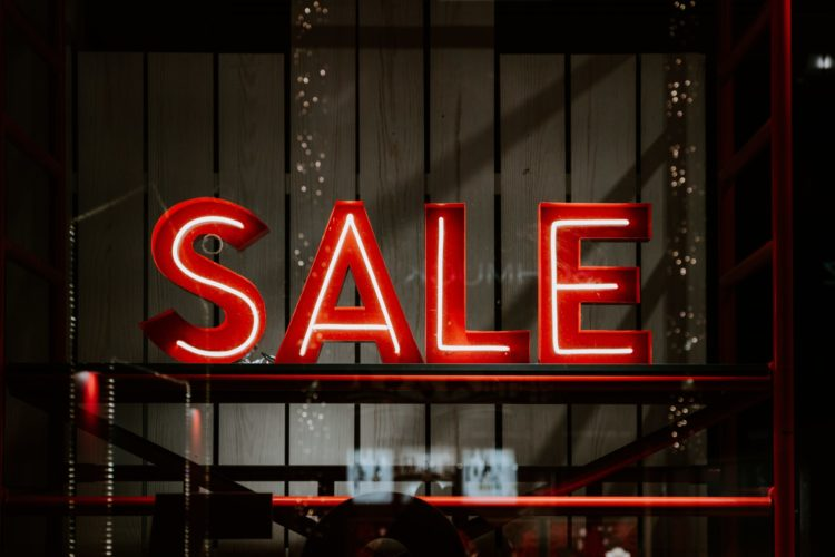 A red neon Sale sign is seen in a store window