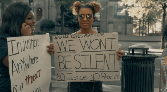 Two smiling black women stand holding handmade signs reading #Blacklives matter We Won't Be Silent NO Justice NO Peace and Injustice Anywhere is a Treat to Justice Everywhere