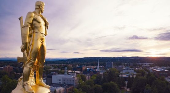 A golden statue of a male dressed as a pioneer holding an ax is seen atop the capitol in Salem Oregon, high above the tree lined mountain horizon