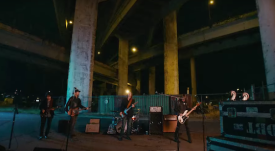 The Drive By Truckers stand beneath a freeway overpass playing their instruments