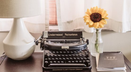 typewriter on desk with lamp and sunflower in a vase and a file of papers