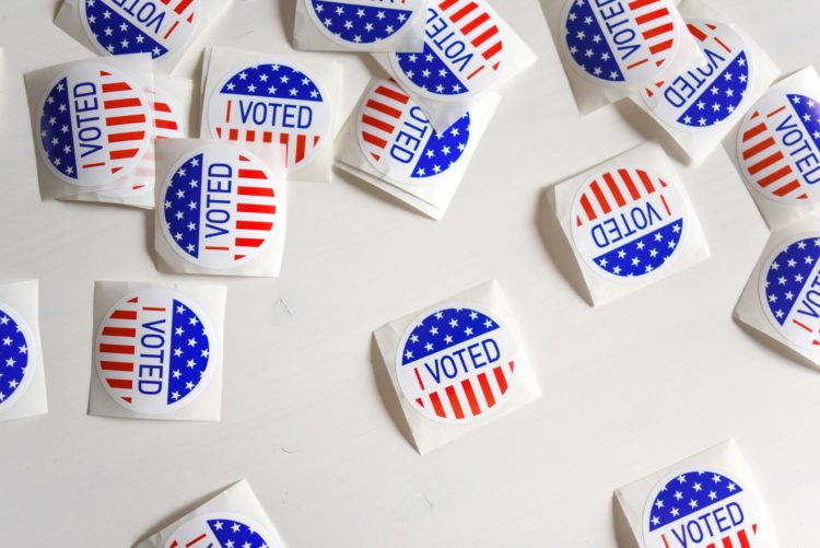 """A scattering of small round stickers reading """"I voted"""" lay on a white table"""