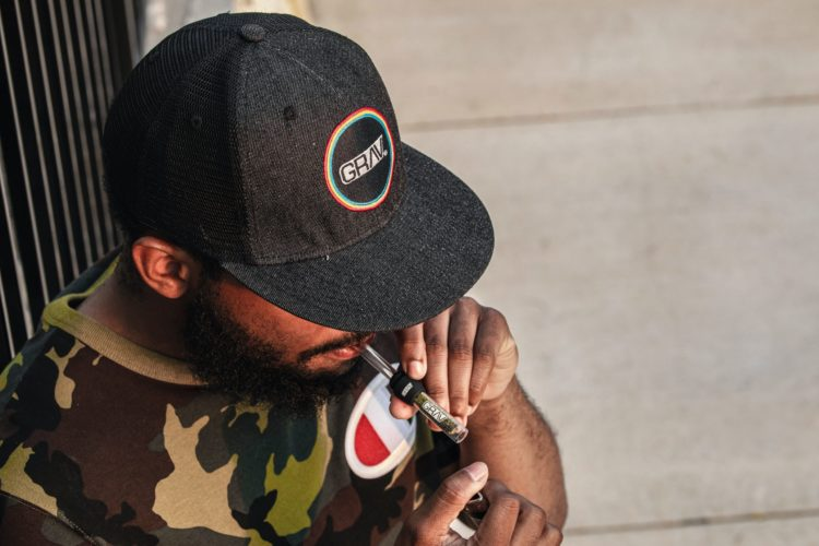 A black man in a baseball cap holds a lighter up to a glass one hitter