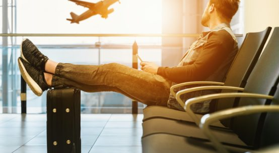 A man sits in a row of chairs at an airport, his feet propped up on a piece of luggage. He looks out a window at a plane taking off.