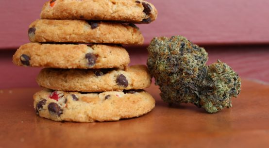A stack of 5 chocolate chip cookies sits next to a single bud of cannabis