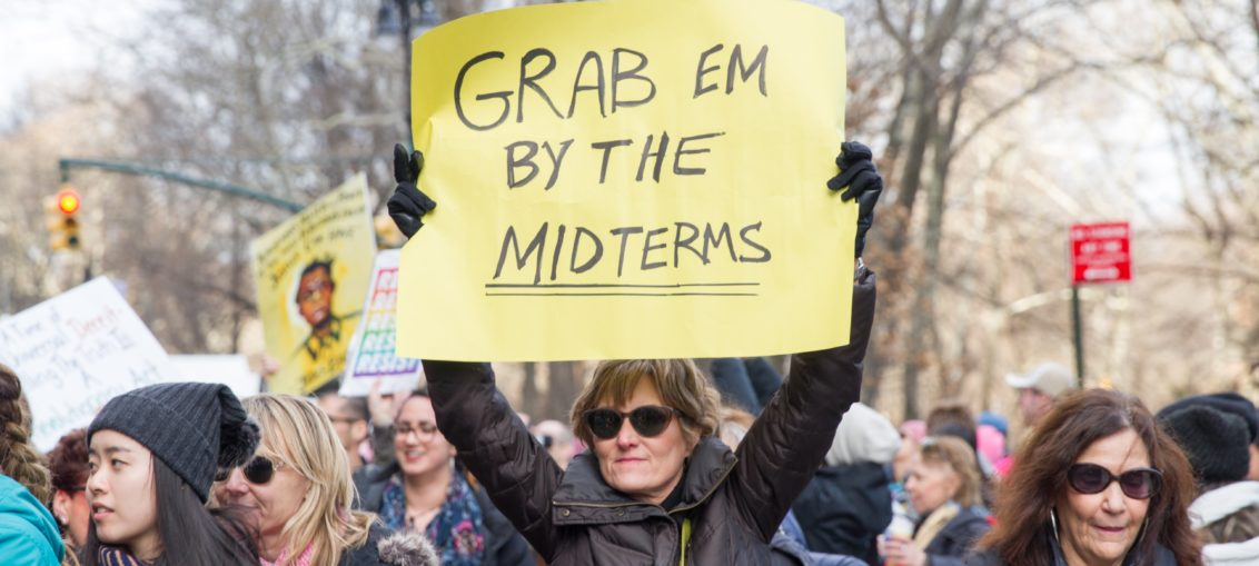 I middle aged woman wearing a black jacket and dark sunglasses holds up a yellow handmade sign reading Grab Em By The Mid Terms. she is in the middle of the Million Woman March.