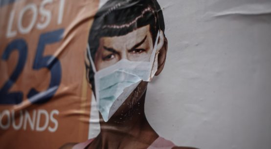 A mural of the character Spock from Star Trek has a surgical mask someone has attached which is fluttering in the breeze.