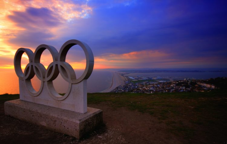 A statue of the five Olympic Rings sits above the ocean at sunset