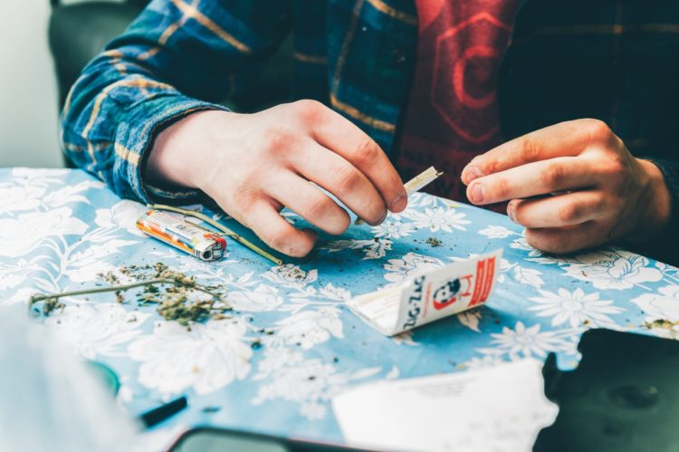 Man rolling a joint with zig zag papers