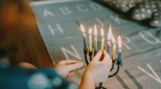 a hand lights the final candle of a Menorah