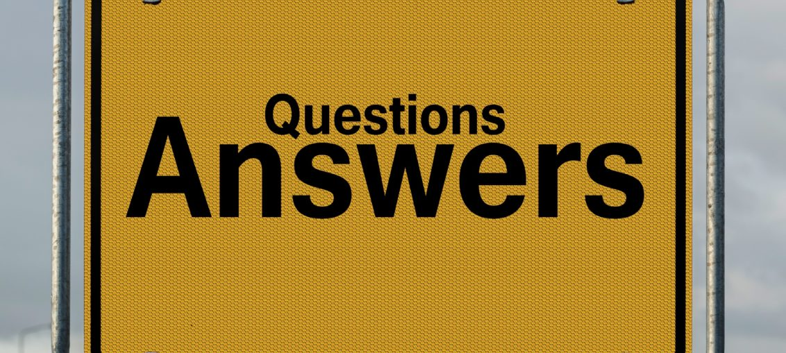 """A yellow highway sign reads """"Questions Answers"""""""