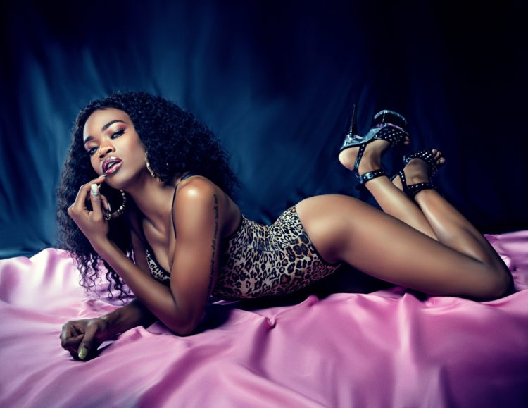 A Black woman in lingerie lays upon a pink silk sheet on a bed posing in a boudoir photography style