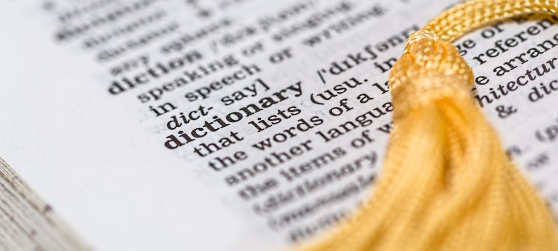 A dictionary is open to the word dictionary, with a yellow tassel bookmark laying across the page