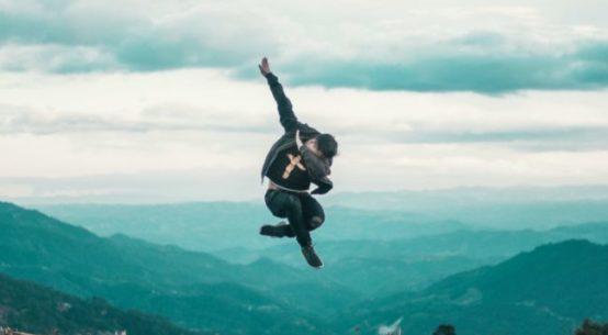 """A man jumps and does """"the Dab"""" high above a city"""